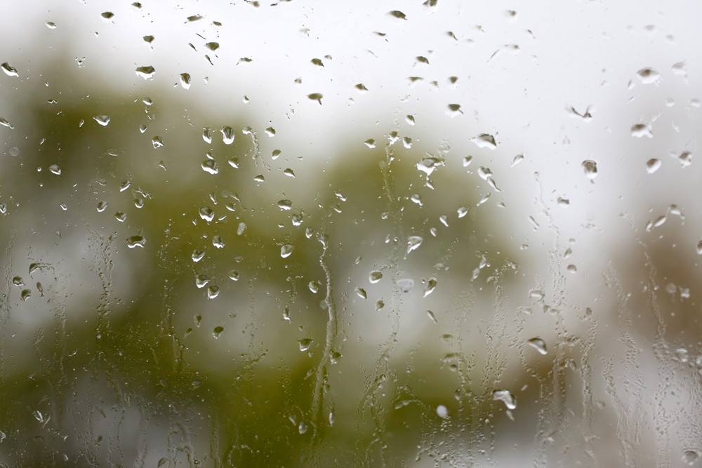 Close up of the rain drops collecting on a window pane on an overcast day.