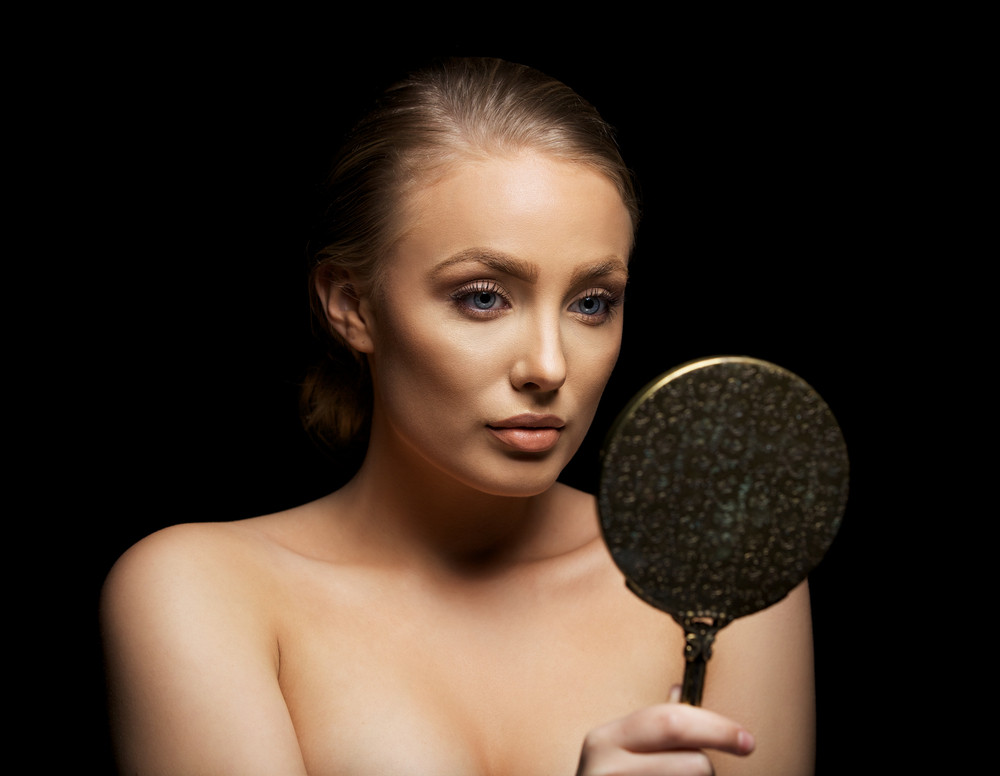Close up portrait of a sexy young woman admiring her beautiful skin in a mirror. Caucasian female fashion model looking in make up mirror against black background.