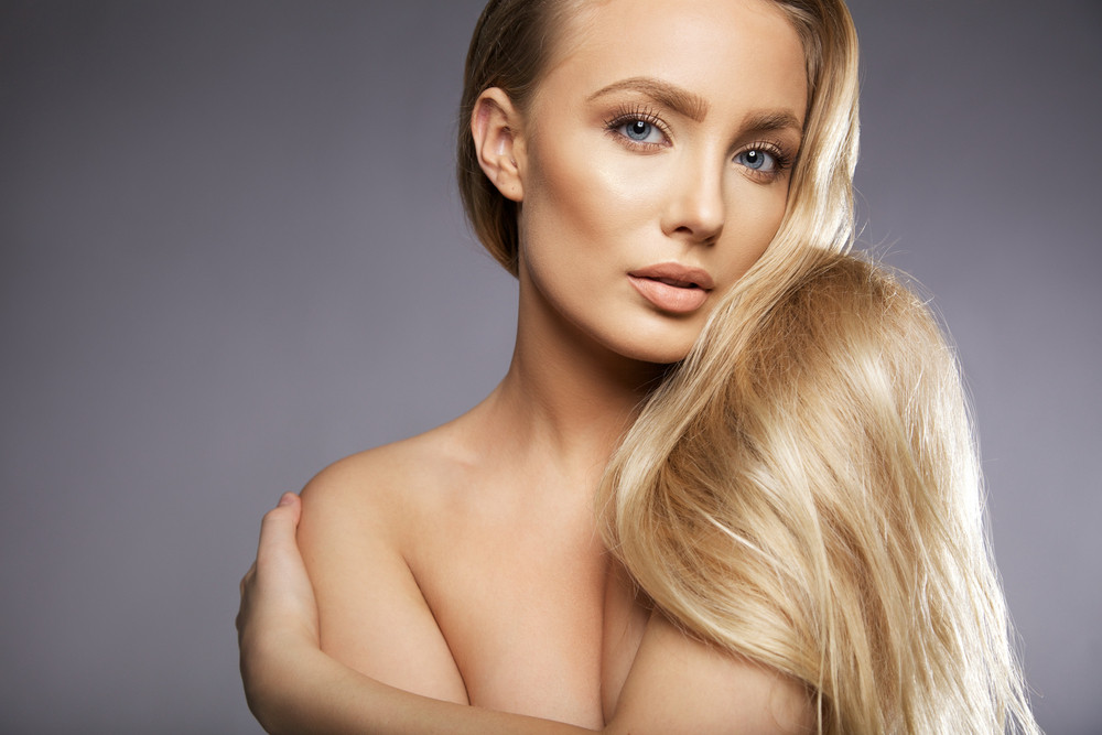 Close up portrait of attractive young woman topless looking at camera. Young caucasian female model with long blond hair against grey background, with lots of copy space.