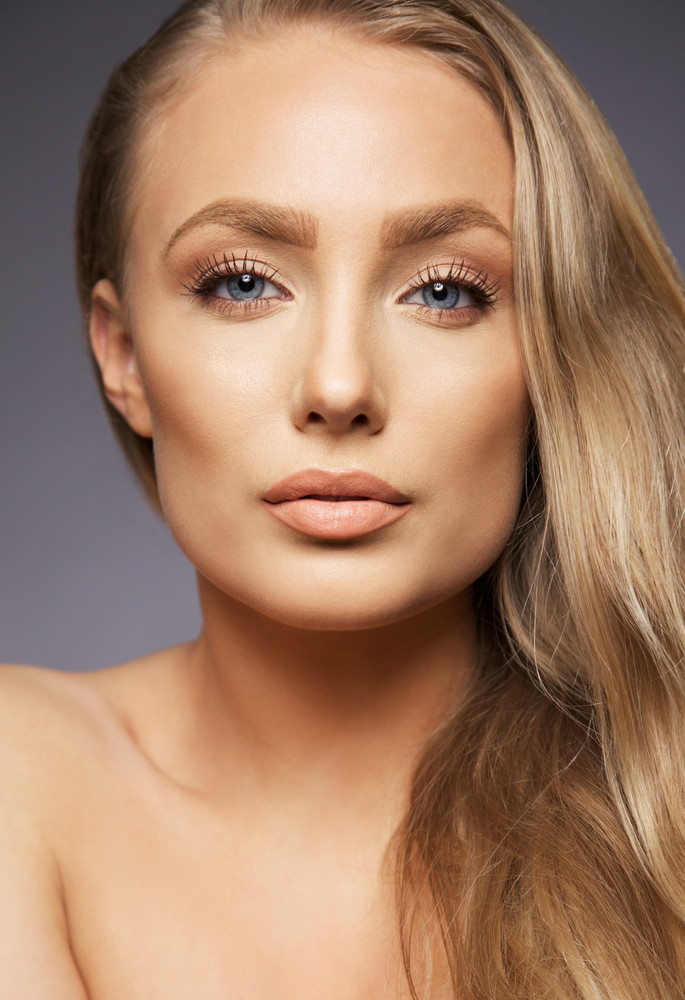 Close up portrait of pretty blond woman on grey background. Perfect face and makeup. Looking at camera.