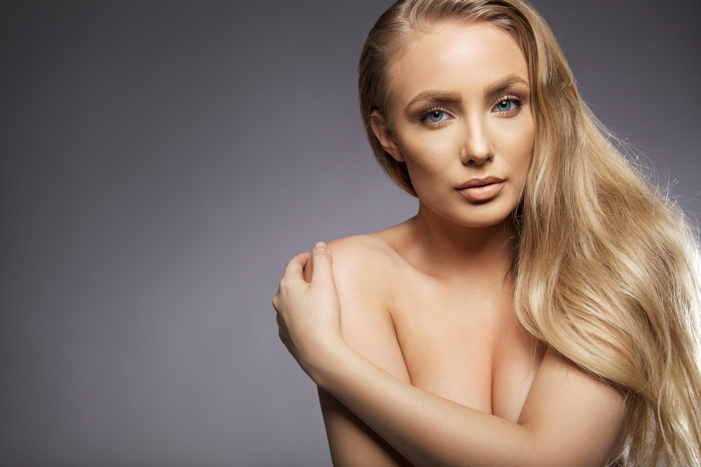 Close up portrait of young woman topless covering her breast with her hand. Young vulnerable female model with long blond hair looking at camera against grey background, with lots of copy space.