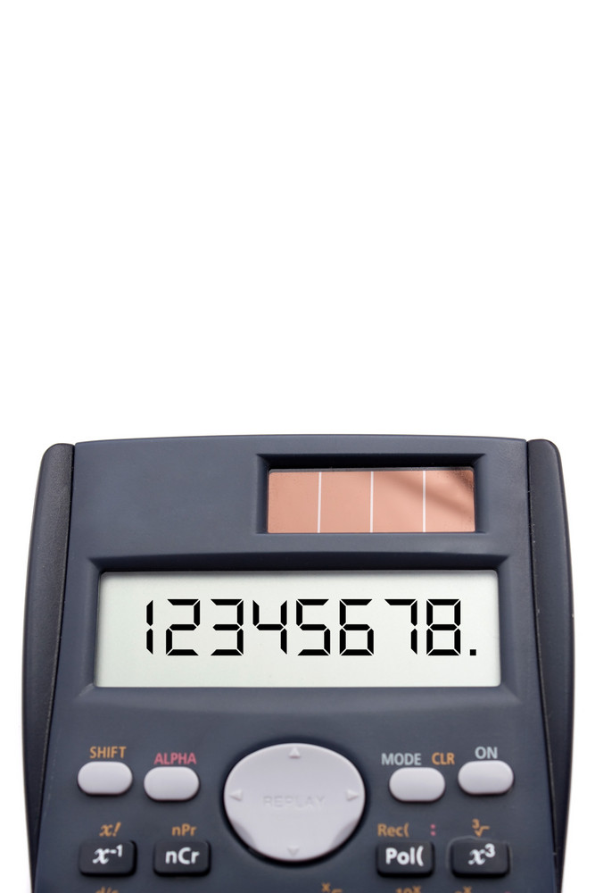 Close up view of a scientific calculator screen with numbers on it isolated over white.  Shallow depth of field.