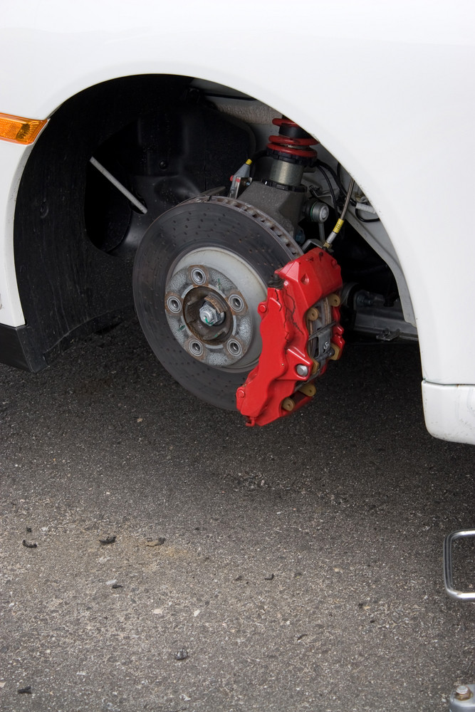 Closeup detail of the wheel assembly and six piston calipers on a modern sports car braking system. The rim is removed showing the front rotor and caliper.