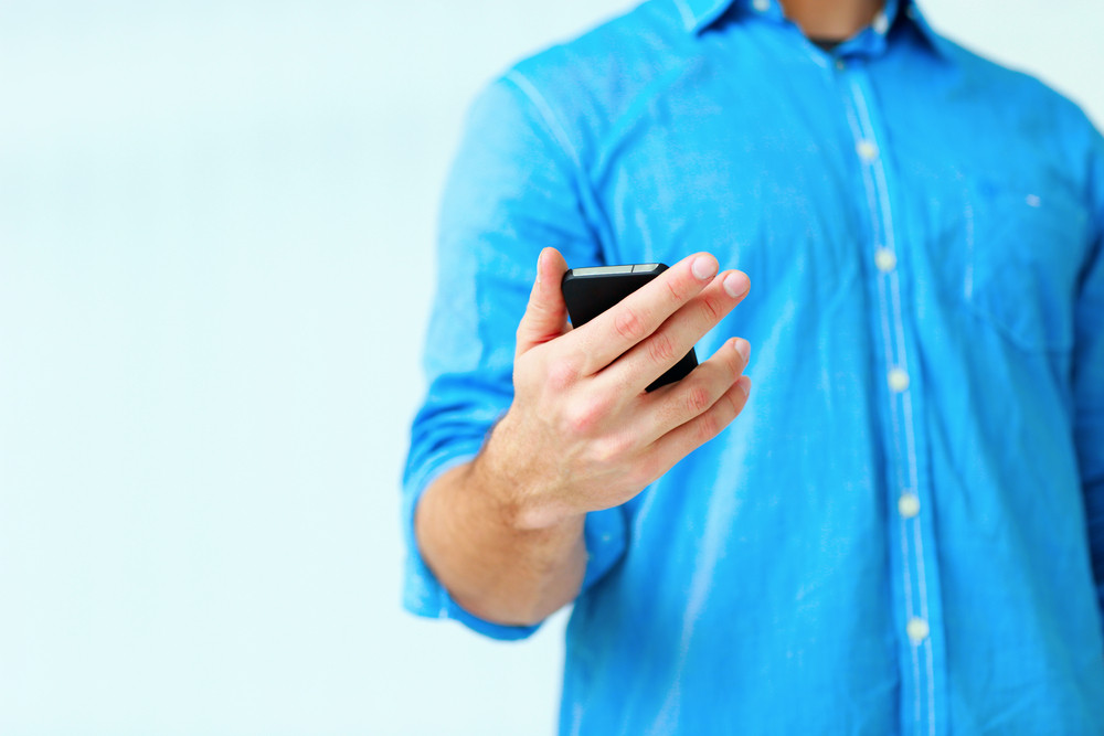 Closeup image af a man holding smartphone isolated on a white background