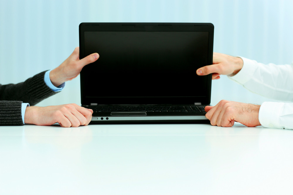Closeup image of a business hands holding a laptop blank screen