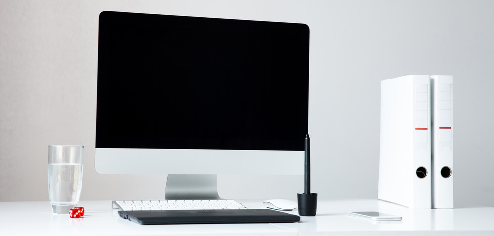Closeup image of a computer on the table with blank screen in office