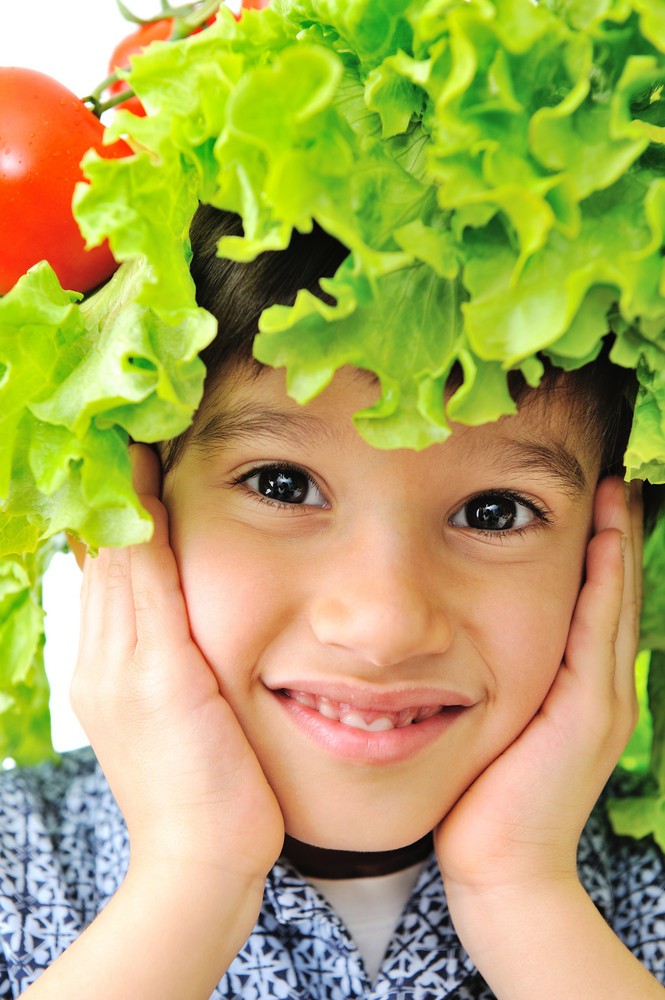 Closeup image of a little kid with tomato and salad hat on his head