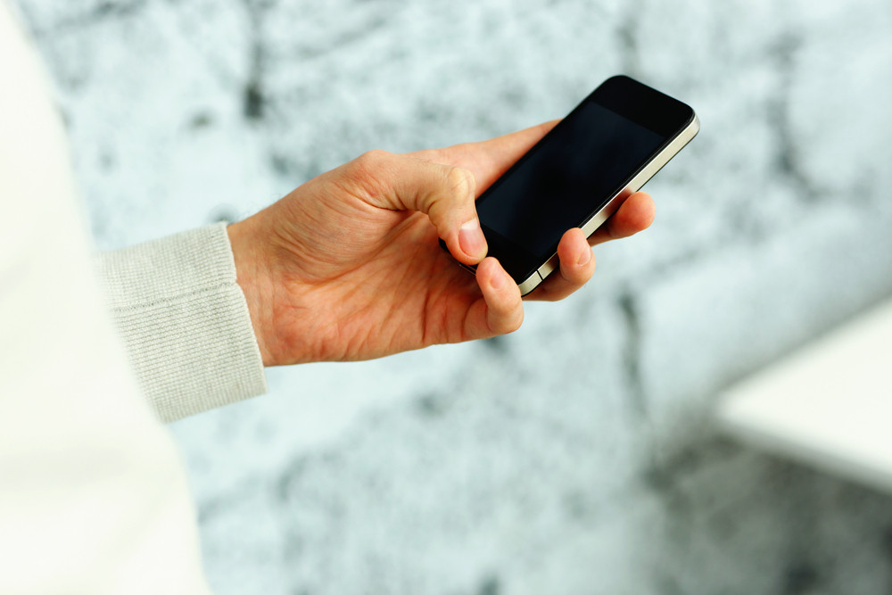 Closeup image of a male hand holding smartphone near the brick wall