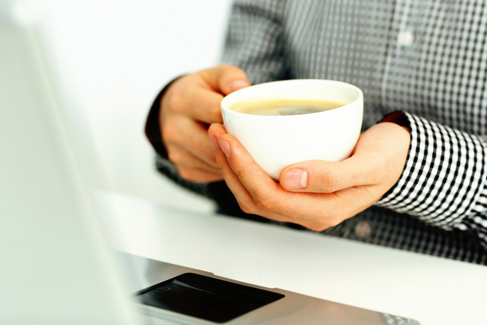 Closeup image of a male hands holding cup of coffee