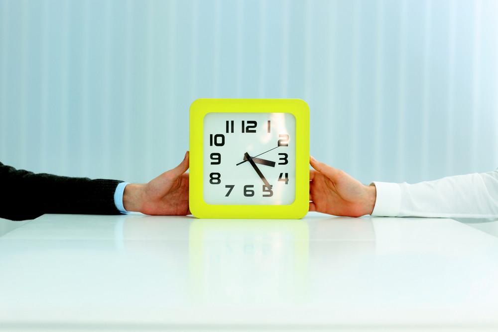 Closeup image of business hands holding clocks