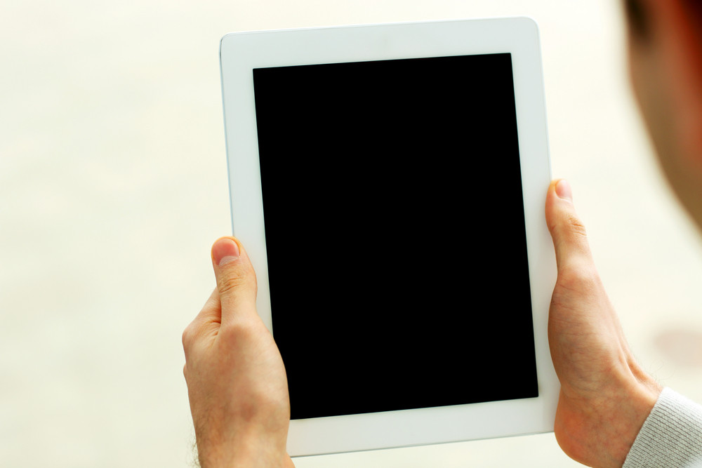 Closeup image of male hands showing display of tablet computer isolated on a white background