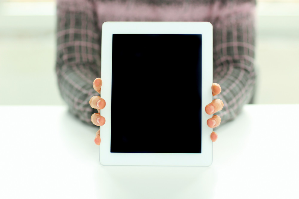 Closeup image of male hands showing display of tablet computer