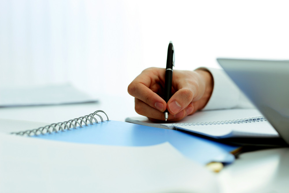Closeup image of mans hand writing in notebook