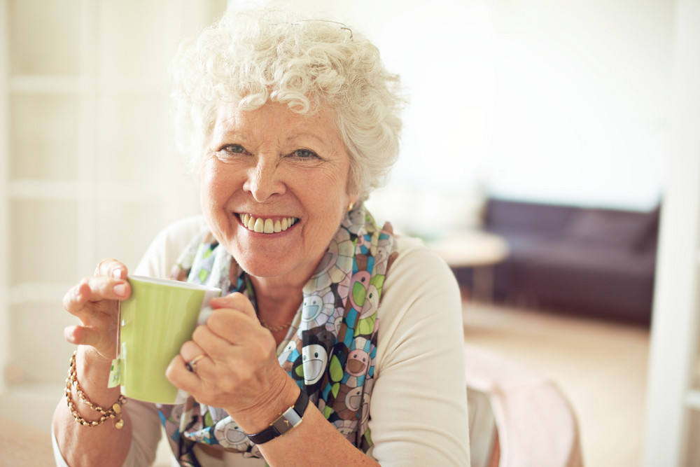 Closeup of a charming old lady drinking her tea