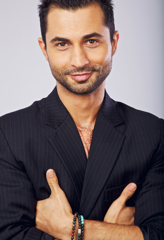 Closeup of a goodlooking man in a studio smiling and looking at you