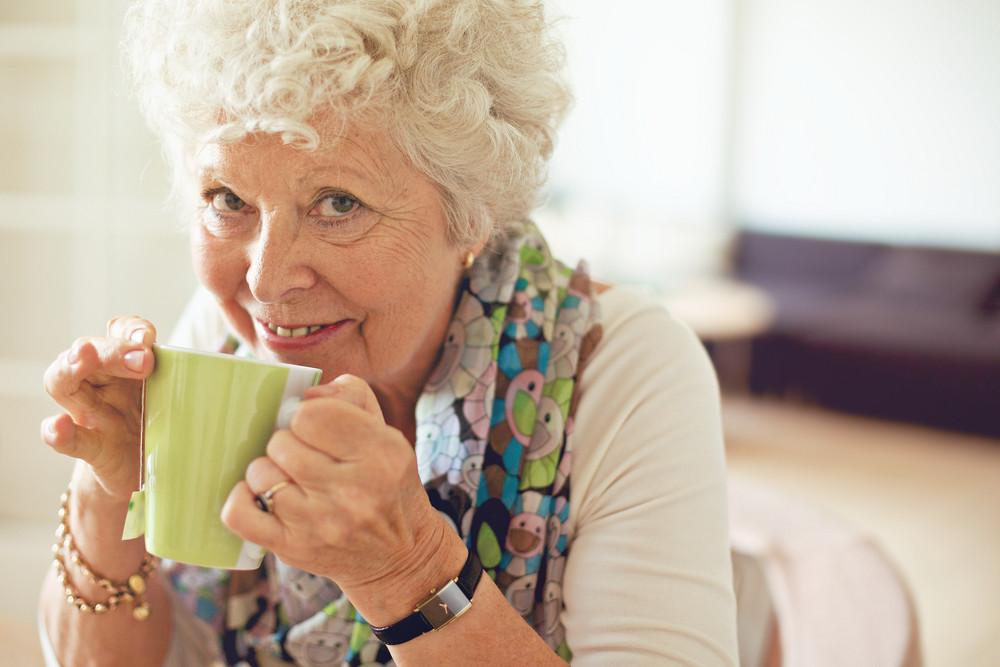 Closeup of a happy senior woman drinking tea
