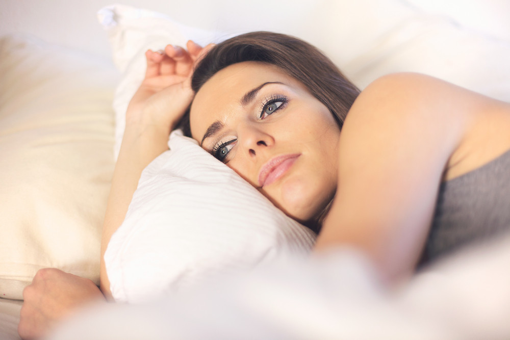 Closeup of a pensive woman lying on bed resting