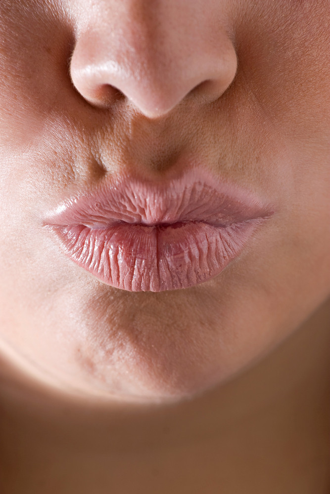 Closeup of a womans full lips puckered up and ready to kiss.