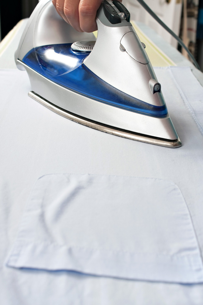 Closeup of and iron pressing and ironing a pocketed dress shirt on an ironing board.
