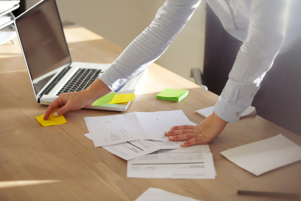 Closeup of businesswoman checking notes on post it. Female executive in office with sticky notes and laptop with documents on desk.