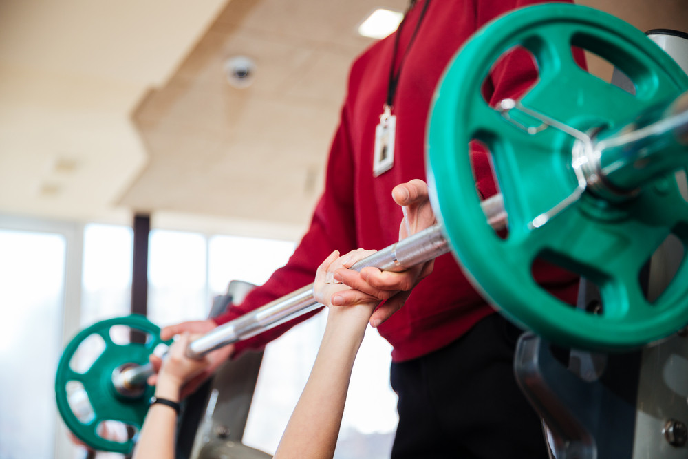 Closeup of hands of young sportswoman training with fitness instructor using barbell  in gym