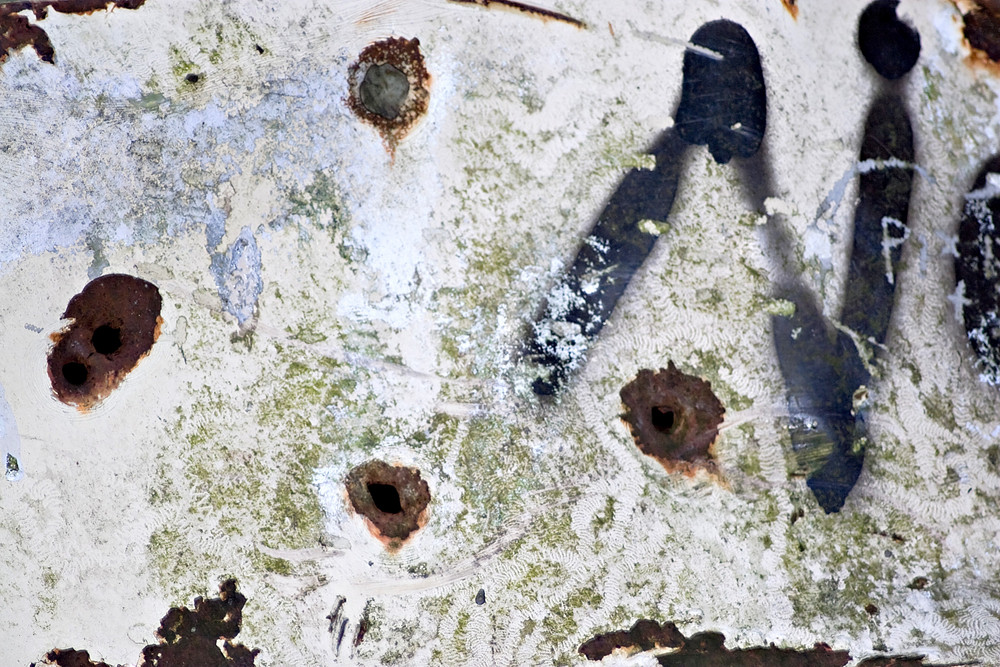 Closeup of rusted metal with chipped paint and bullet holes.