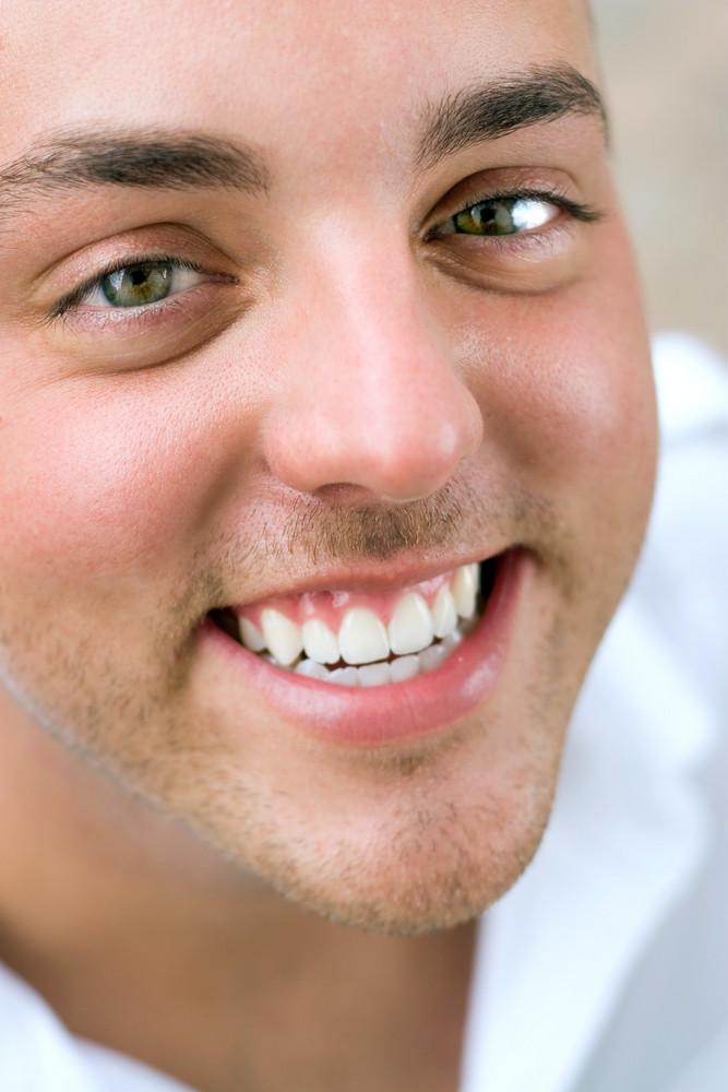 Closeup of the face of a happy young man with incredibly white teeth.