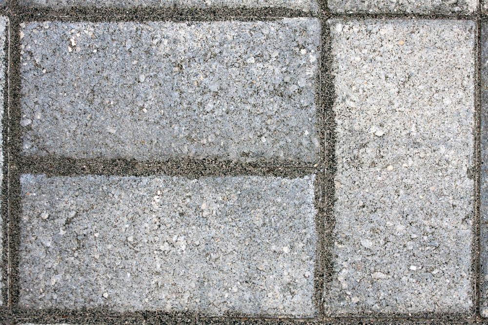 Closeup of three paver bricks in a paved stone patio floor.