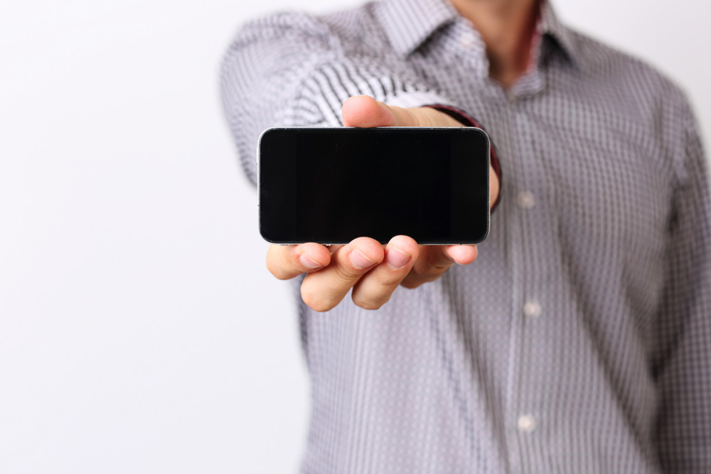 Closeup portrait of a male hand showing smartphone screen