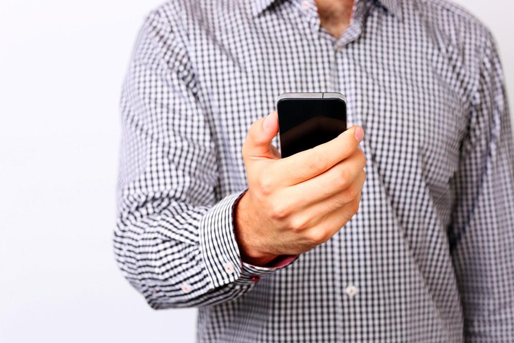 Closeup portrait of a male hand using smartphone