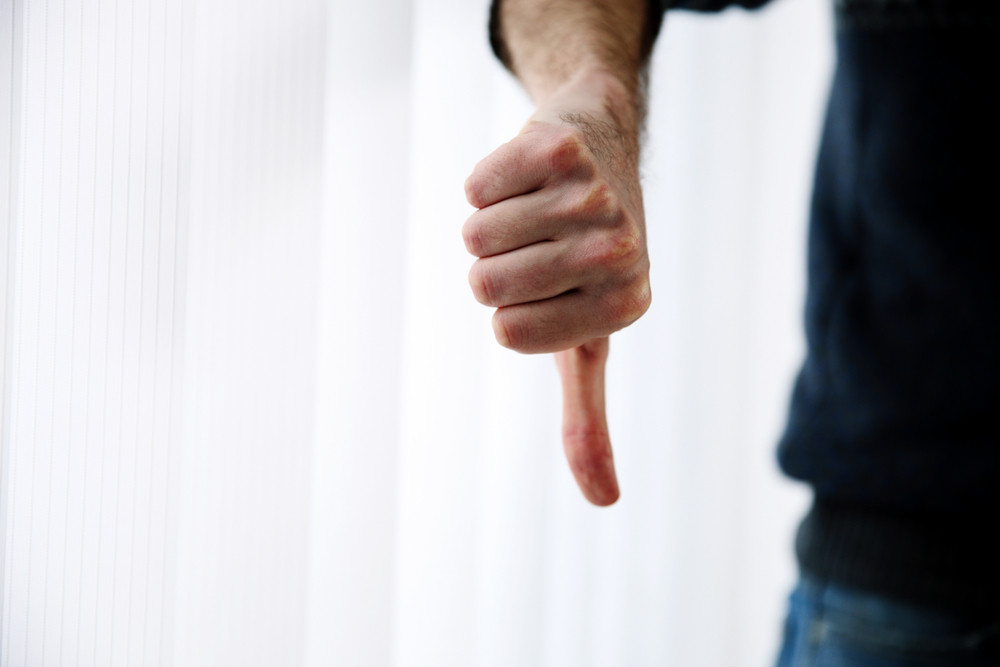 Closeup portrait of a male hand with thumb down