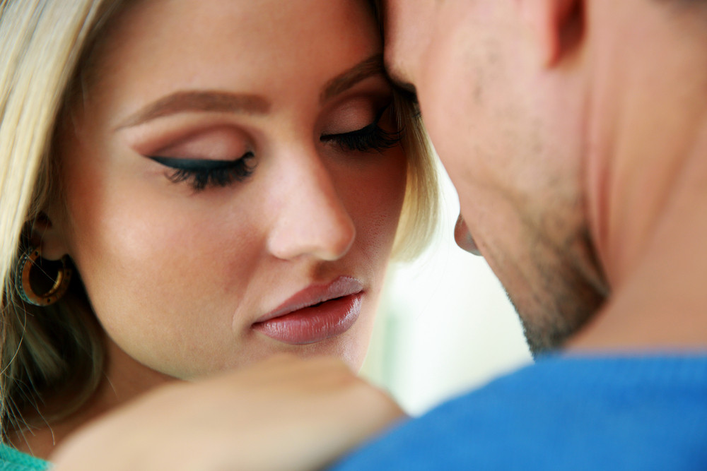Closeup portrait of a man and a woman face to face with eyes closed