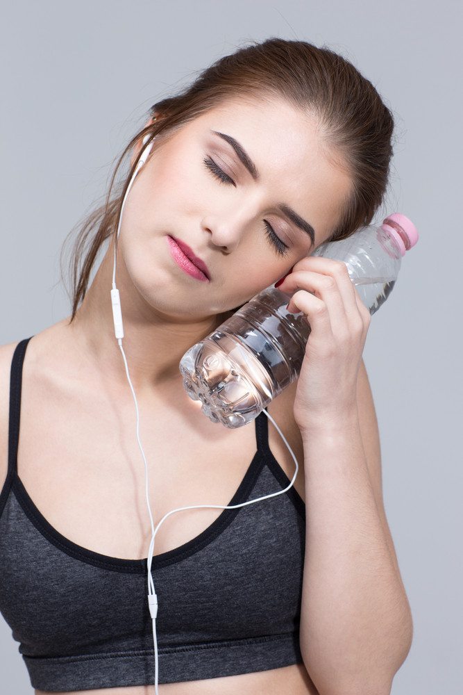 Closeup portrait of a sporty woman with bottle of water