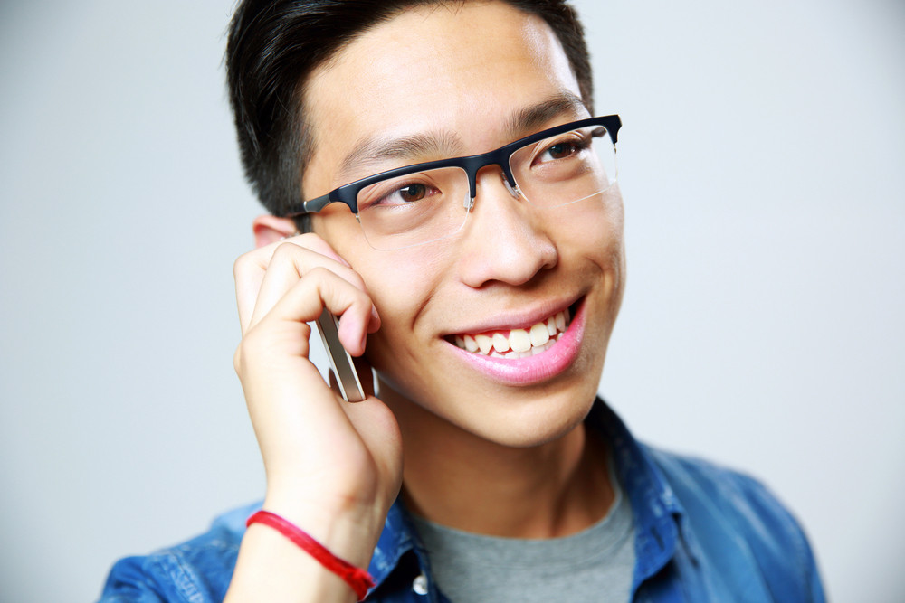 Closeup portrait of a young asian man talking on the phone