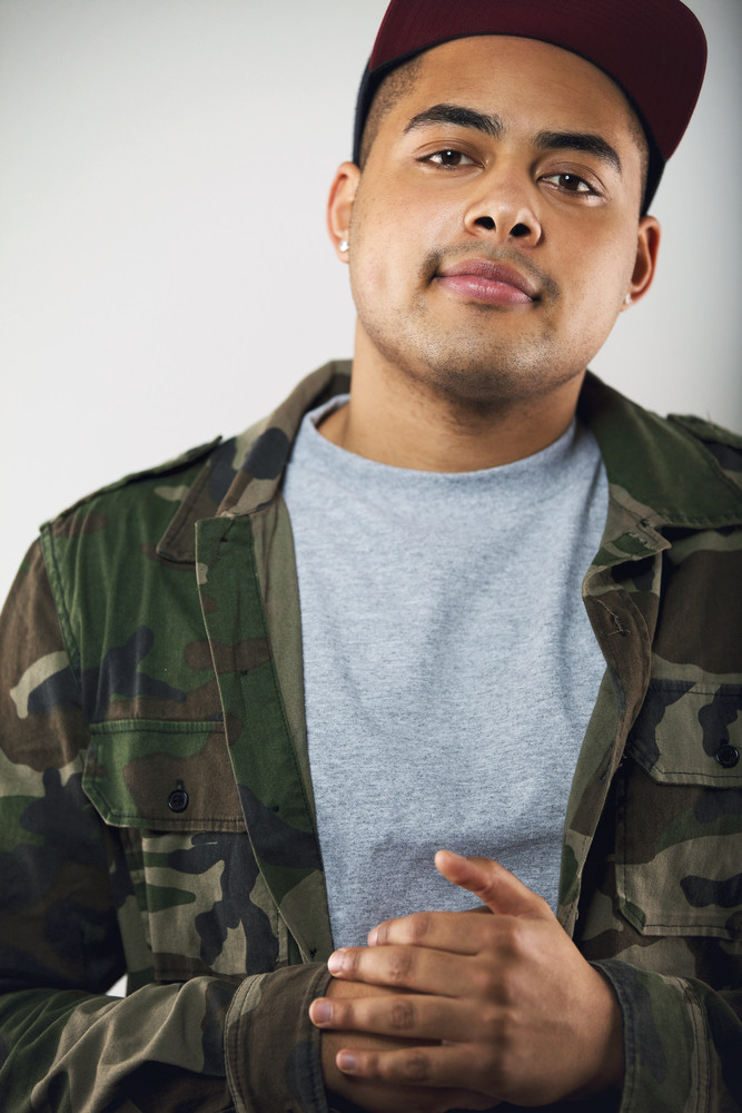Closeup portrait of young man in casuals. Young male model wearing camouflage jacket and cap on grey background