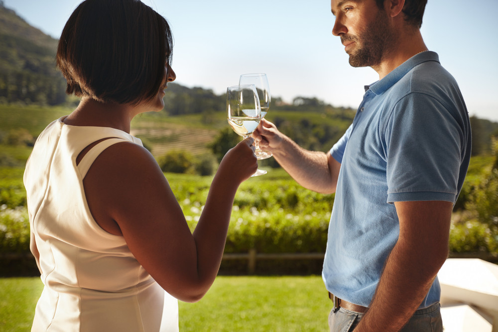 Closeup shot of young couple toasting wine while standing outdoors at winery restaurant with vineyard in background. Man and woman celebrating with wine on vacation .