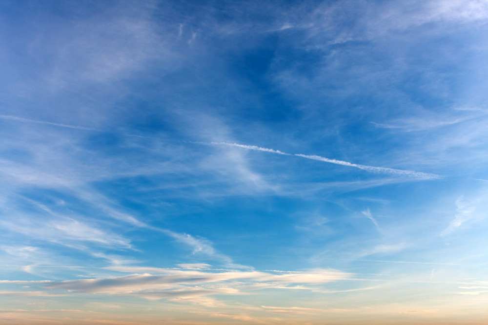 Clouds with airplane exhaust streams showing lines of pollution stretched across the sky.