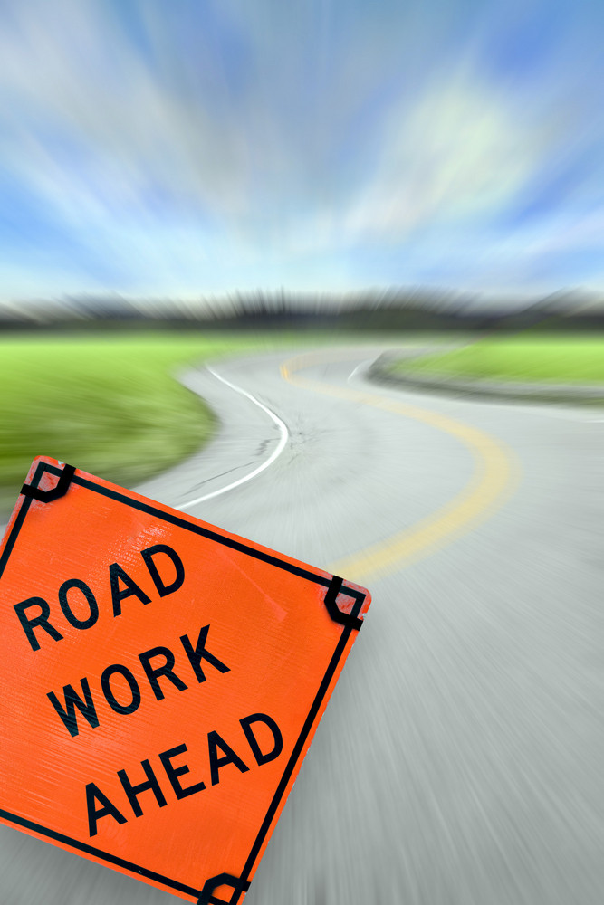 Colorful abstract illustration of a highway at high speeds traveling towards a city horizon with a sign that reads ROAD WORK AHEAD in the foreground.