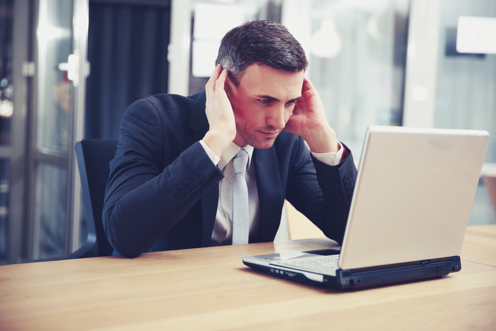 Concentrated businessman sitting with laptop at office