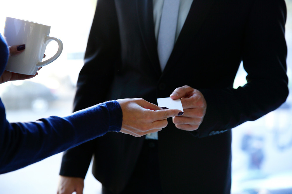 Concept shot of exchange business card between man and woman