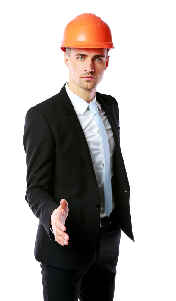 Confident businessman in helmet offering handshake over white background