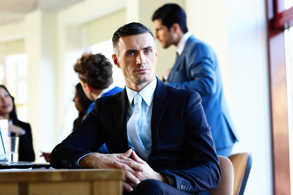 Confident businessman sitting at the table with colleagues on background