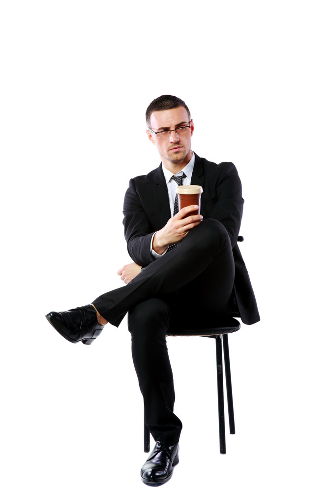 Confident businessman sitting with cup of coffee over white background