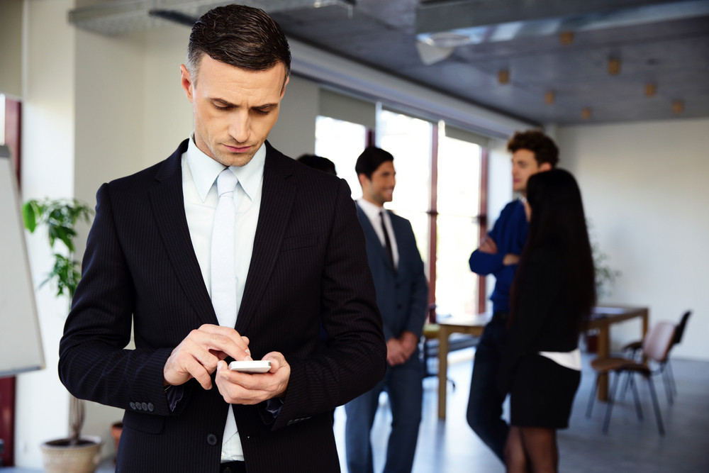 Confident businessman using smartphone in front of a colleagues