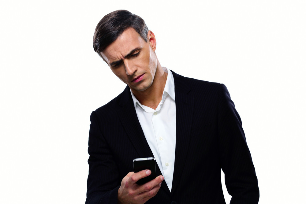 Confident businessman using smartphone over white background