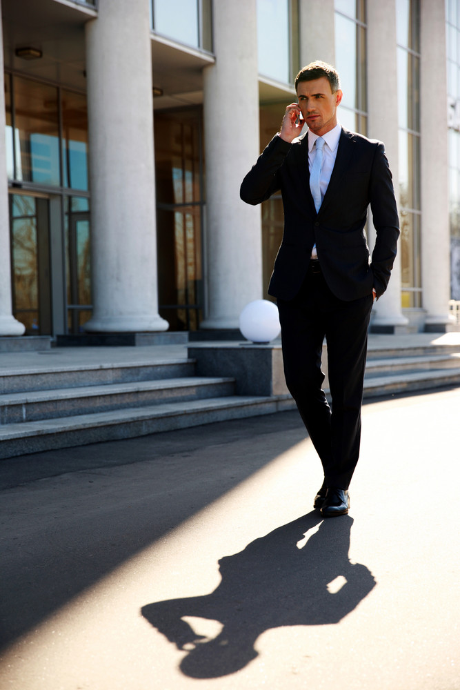 Confident businessman walking on the street and talking on the phone