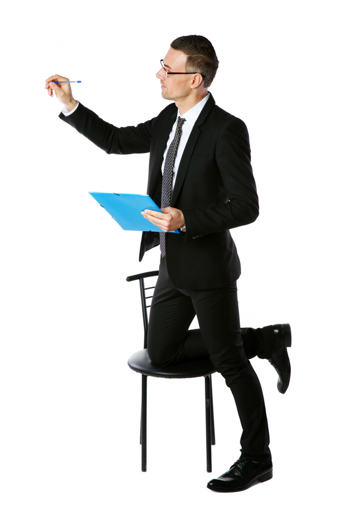 Confident businessman writes with pen at copyspace over white background