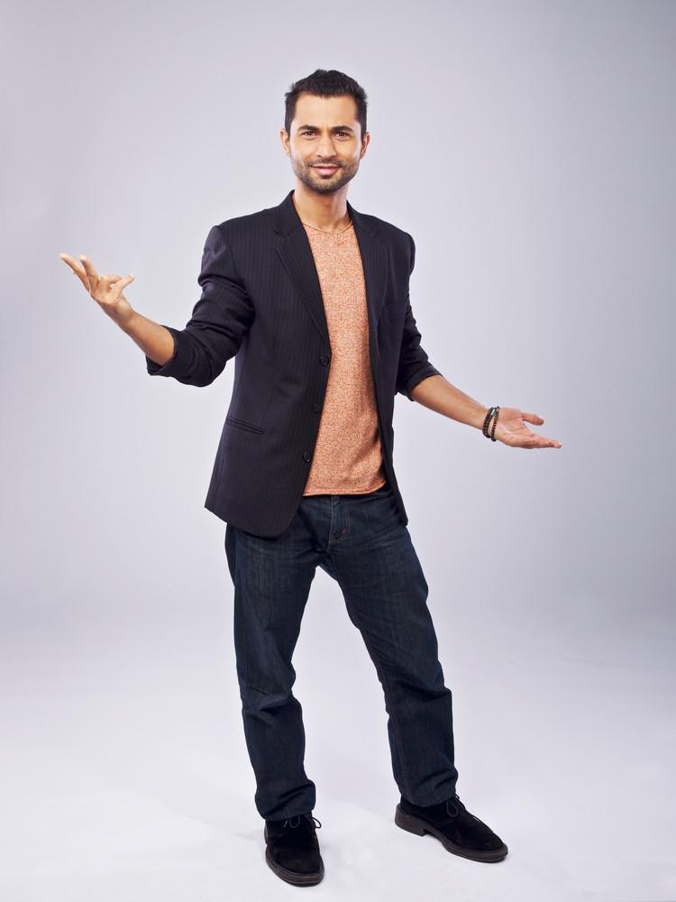 Confident man standing in a studio doing hand gesture