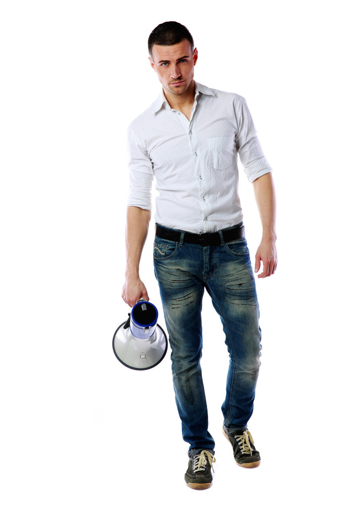 Confident man standing with megaphone over white background