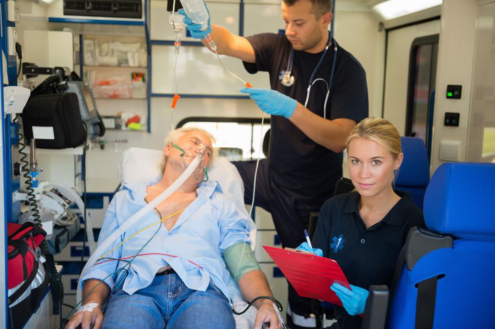 Confident paramedic treating injured elderly patient on stretcher in ambulance
